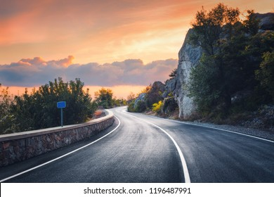 Mountain road at sunset. Landscape with rocks, orange sunny sky with clouds and beautiful asphalt road in the evening in summer. Vintage toning. Travel background. Scenery with highway. Transportation