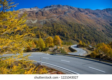 Mountain road in Switzerland. Bernina mountain pass street on a beautiful autumn day. Road through the alps in Europe. Fantastic sunny day for a road trip with a car. Curved mountain road.