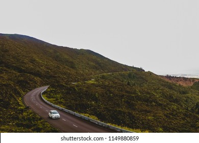 Mountain road that leads to lake of fire in Azores. A beautiful green landscape with a single white car on a sinuous road.