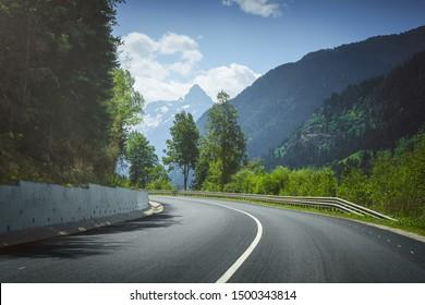 mountain road. travel through woodland to icepeaks.