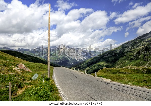 Mountain road under cloudy sky.