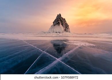 Mountain rock on frozen water lake with sunset tone, Baikal Russia winter season natural landscape background