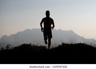 Mountain runner in silhouette in a suggestive landscape.