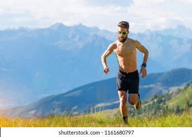 Mountain runner trains on bare-chested meadows.