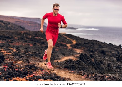 Mountain running ultra runner man athlete training cardio outdoor in extreme conditions on volcanic trail in coast landscape. Wet red rocks. Sports athlete wearing compression clothes and shoes.