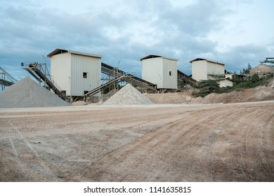 a mountain of sand lies in the concrete factory where and a conveyor belt for transporting the sand