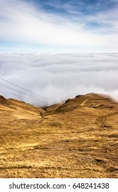 A mountain scene with clouds cover on a mountain hill. Cable seen in the foreground.