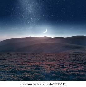 Mountain scene with twilight sky, Moon and shining stars of Milky Way