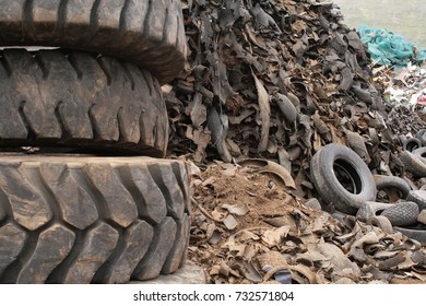 A mountain of scrap pneumatics in a junkyard. Crushed and old tires. Background unfocused.