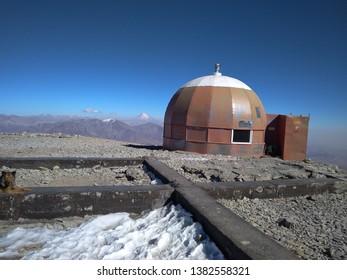 Mountain shelter on mt. Tochal summit (Alborz mountains near Tehran, Iran) with view on mount Damavand (highest peak of Iran) in background
