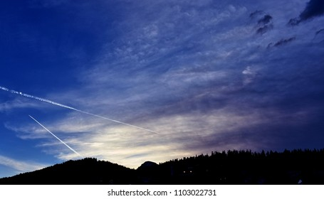 Mountain silhouette against blue evening sky with two contrails