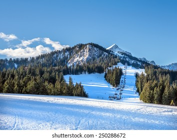 Mountain skiing slopes and ski lift at Hausberg top near Garmisch-Partenkirchen town in Bavarian Alpes in Germany with Zugspitze peak and blue sky at the backdrop on a clear winter day