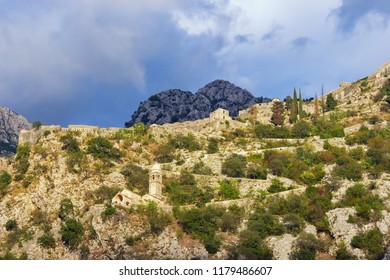 Mountain slope with ancient fortifications. Montenegro, view of road to Kotor fortress and Church of Our Lady of Remedy