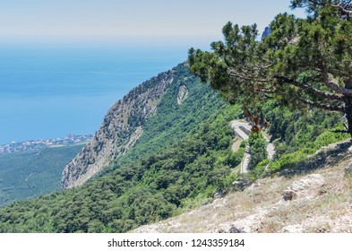 Mountain slope with a road near the sea coast. Russia, Republic of Crimea. 06.13.2018. The slope of Mount Ai-Petri with a highway and views of the Black Sea