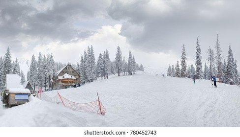 Mountain slope with ski piste and ski lifts among spruce forest on ski resort in Carpathian Mountains