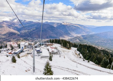 Mountain slopes with chairlift on a winter sunny day. Winter mountains panorama with ski slopes and ski lifts near ski center.