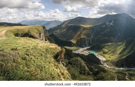 The mountain slopes are covered rays of the sun, which make their way through the clouds. View from the top of the mountain. In the valley of the blue mountain lake