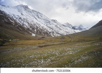 Mountain with snow covered with yellow field below and cloud, Kargil ,Jammu and Kashmir, India