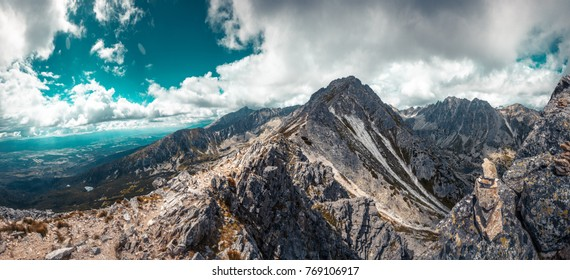 Mountain stone range peak against blue cloudy sky. Nature landscape. Travel background. Holiday, hiking, sport, recreation. National Park High Tatra, Slovakia, Europe. Vintage retro toning filter