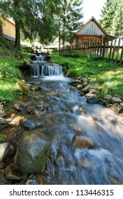 Mountain stream flowing beside houses.