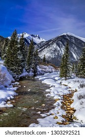 Mountain stream flowing with water in valley along Red Mountain Pass in Colorado near the town of Silverton after freshly fallen snow on sunny morning