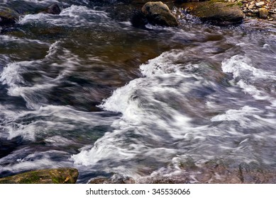 Mountain stream river with rapids under the bridge