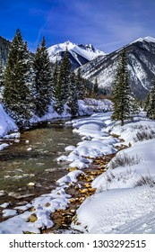 Mountain stream in winter with freshly fallen snow covering mountain valley landscape