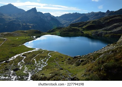 Mountain streams run to the alpine lake Roumassot in the Bearn Pyrenees. The sky is reflected in the mirror surface of the lake and brooks.