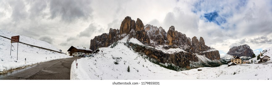 Mountain street of Gardena Pass with snowy landscape on the mountains of Group of Sella and cloudy sky, Gardena Valley - Trentino-Alto Adige, Italy