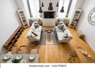 Mountain style living room with wood parquet, two sofas and dining table