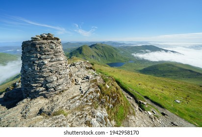 The mountain summit cairn of Ben Lawers with the summits of Creag an Fhithich and An Stuc in the distance with Lochan nan Cat below in the Scottish Highlands, UK landscapes.