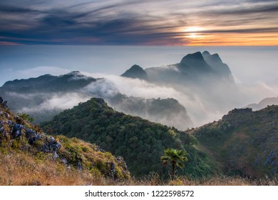 Mountain summit  in sunset time  with yellow grass foreground. Sea of fog in between layer of mountain.One of the most beautiful scenic area in Chiangmai, Thailand. Doi Luang Chiang dao mountain