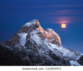 Mountain top at sunrise. Mount Ushba, Svaneti, Georgia, Caucasus. The first rays of the sun. Full moon over the ridge
