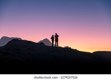 Mountain top in Tenerife at dusk as the sunsets, 2 people stand silhouetted against the sun