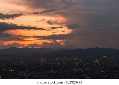 Mountain top view of city night lights in orange sunset clouds