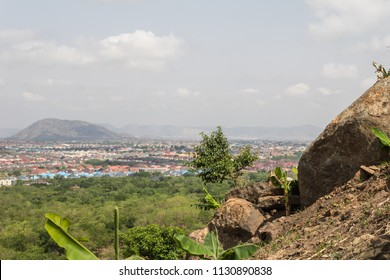 A mountain top view of the landscape, trees, the sky and a city dwelling.
