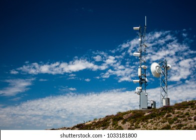 Mountain top weather station with a blue sky and scattered clouds