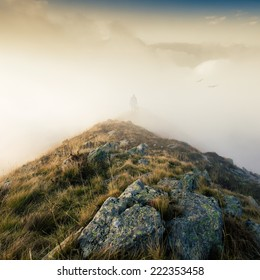 mountain top.man wrapped in fog stands on a mountain peak