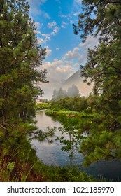 Mountain tops peaking between trees the early morning mist rises off the Wenatchee River near Leavenworth Washington