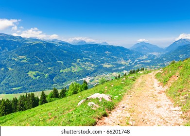 Mountain trail on green  slope under blue sky. French Apls,  Haute-Savoie.