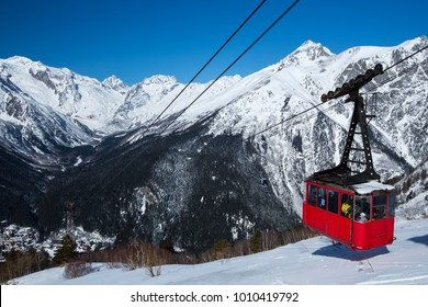 mountain trailer funicular red descends on the background of snow-capped peaks and a mountain valley