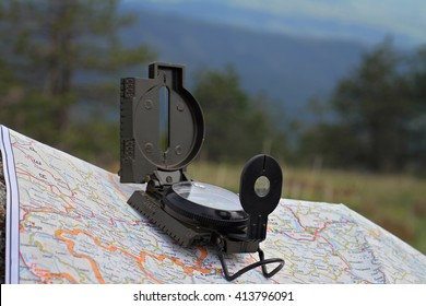 Mountain traveling, wanderlust concept. Road map and compass on mountain rock