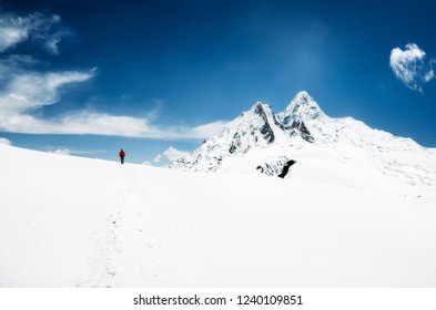 Mountain trekker in Himalayas mountains walking in snow with peaks in background, Annapurna region, Nepal, Asia
