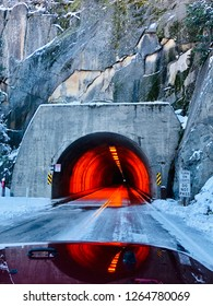 Mountain Tunnel with Red Lighting and Snowy Road on Winter Drive