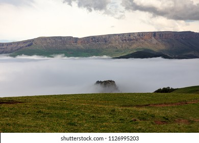 Mountain valley in the fog. The region of Elbrus, Karachay-Cherkessia, Russia. The gorge of the Malka River, the Gyly-Su tract. The place of exit of curative mineral springs and volcanic rocks.