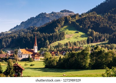 Mountain valley, grass hill pine forest and church in Marbach town Entlebuch UNESCO Biosphere Reserve in central Switzerland