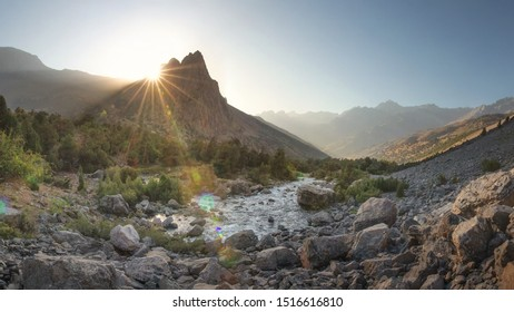 Mountain valley with river. Bright mountains nature landscape at sunrise. Mountain river and vivid sun rays behind mount peak. Scenic highland in warm sunlight