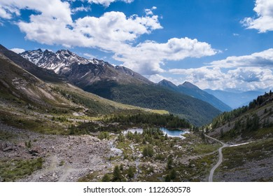 Mountain valley with road and alpine lake