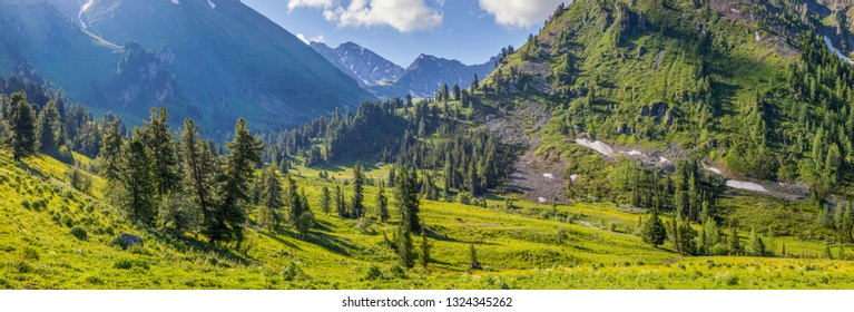 Mountain valley, snow and greens on the slopes. Spring in the mountains, panorama nature.