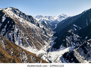 Mountain valley with snow and high peaks against blue sky in Kazakhstan